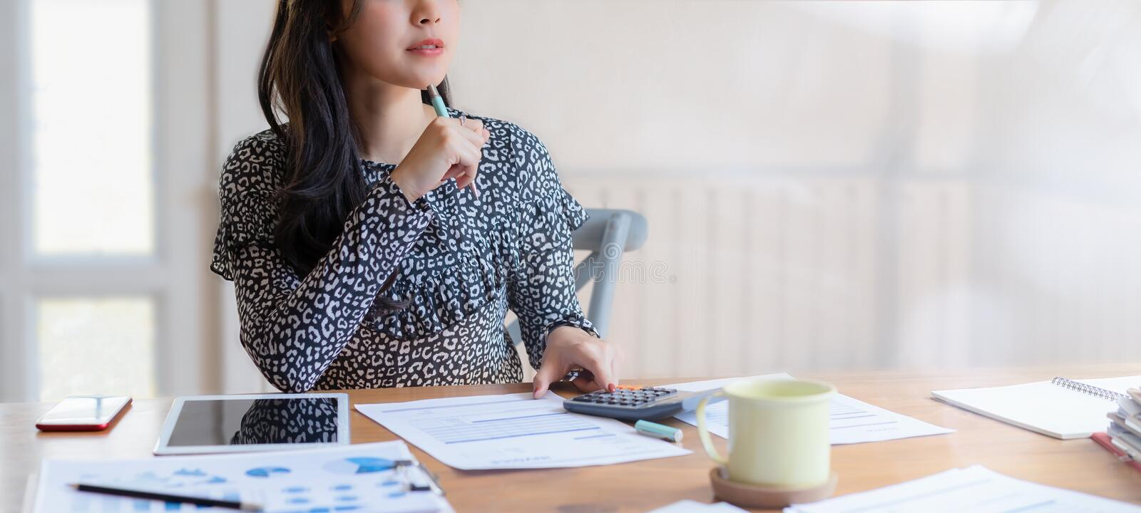 Cropped shot of beautiful asian female accountant using calculator making calculations Savings at home. Working at home concept royalty free stock image