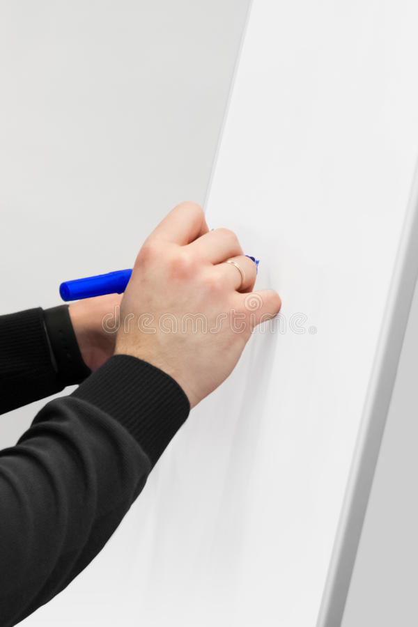 Cropped shot of businessman putting his ideas on white board during a presentation in conference room. Focus in hands with marker royalty free stock photo