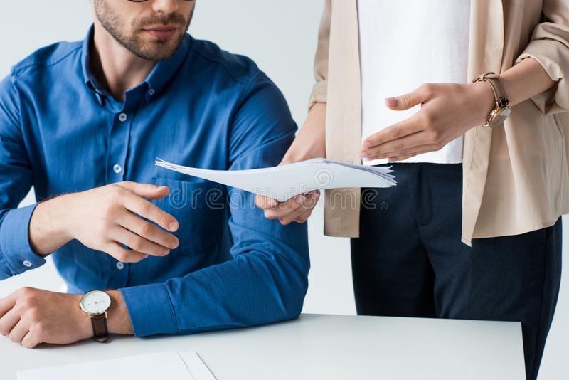 cropped shot of businessman sitting at workplace while his colleague passing documents to him royalty free stock image