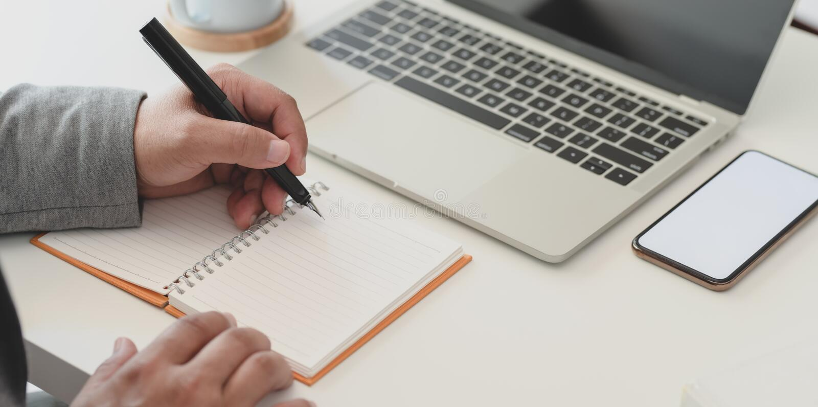 Cropped shot of businessman working his project while writing ideas on notebook stock image