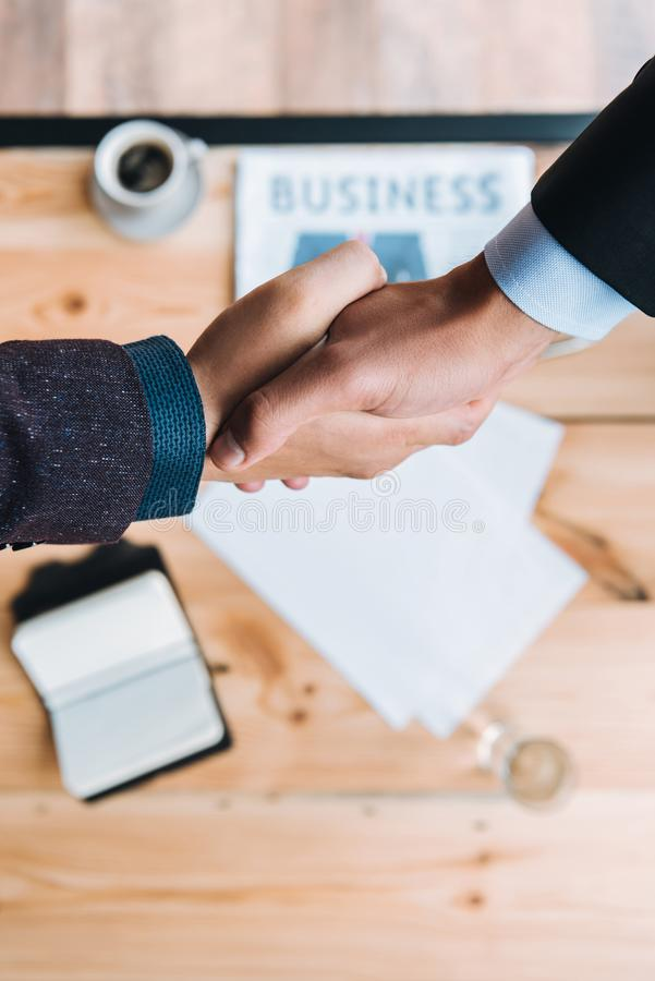 Businessmen shaking hands in cafe stock photography