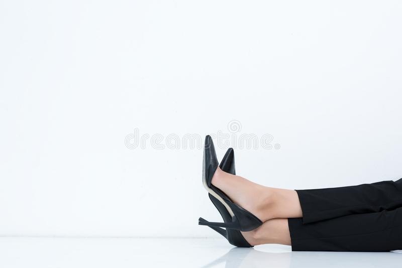 Cropped shot of businesswoman in black pants and high heels laying. On floor stock photo