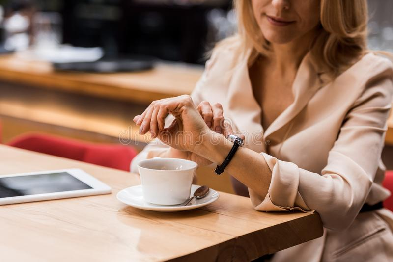 cropped shot of businesswoman checking time while sitting at table with tablet and cup royalty free stock image