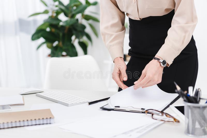 Cropped shot of businesswoman doing paperwork at workplace. In office stock photography
