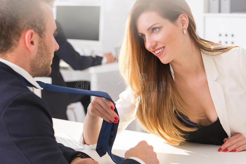 businesswoman holding a man`s tie stock images