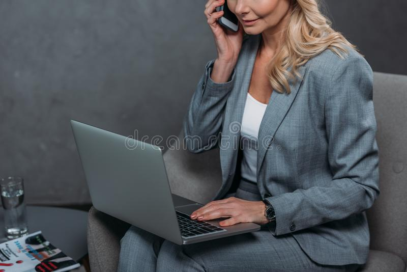 Businesswoman. Cropped shot of businesswoman talking by phone while using laptop stock image