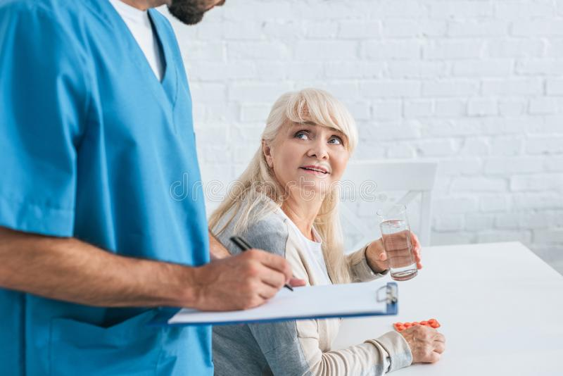 Cropped shot of caregiver writing on clipboard while senior woman. Holding glass of water and pills stock photo