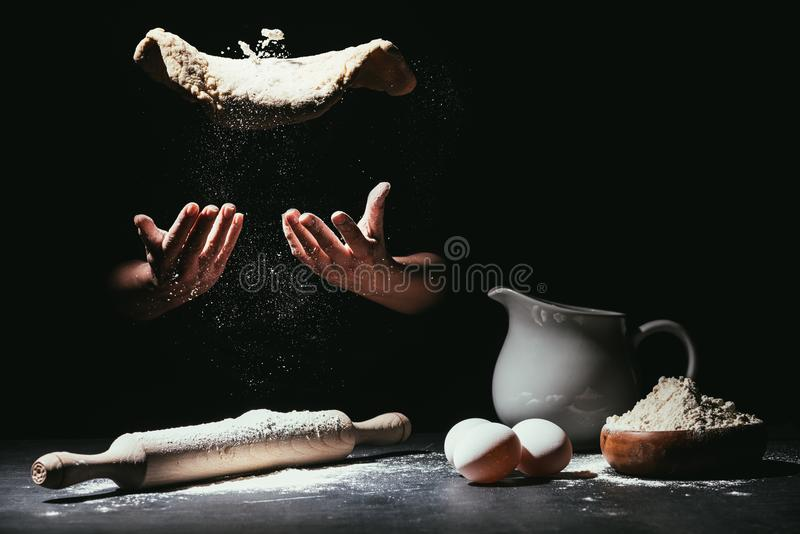 cropped shot of chef throwing up dough for pizza stock photos
