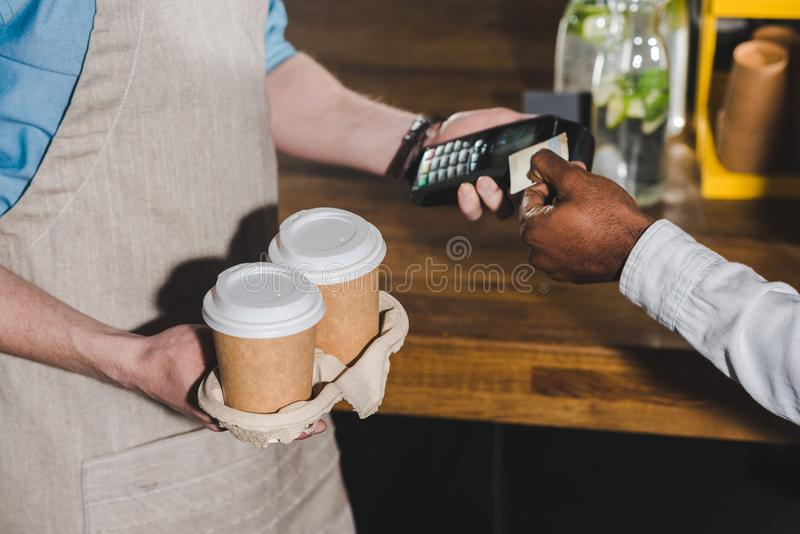 Cropped shot of client paying by credit card and barista with terminal and coffee cups. In hands stock photo