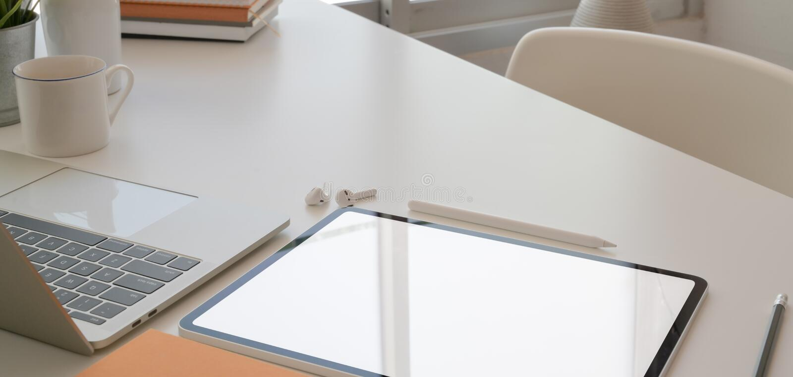 Cropped shot of comfortable workspace with tablet, laptop computer and office supplies royalty free stock photography