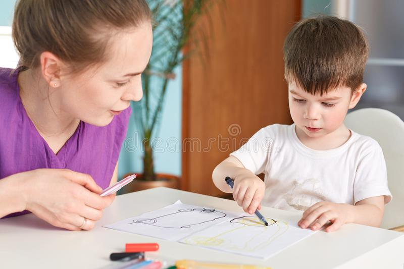 Cropped shot of concentrated small male kid holds colourful marker and makes nice picture by himself, sits near his mother who hel royalty free stock photo