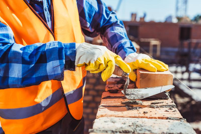 Cropped shot of construction worker in protective gloves laying bricks royalty free stock photo