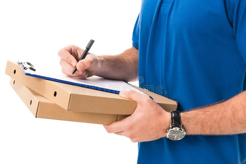 cropped shot of delivery man holding boxes with pizza writing on clipboard stock image
