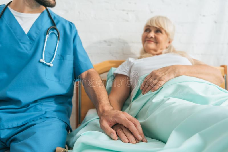 cropped shot of doctor and sick senior woman stock photography