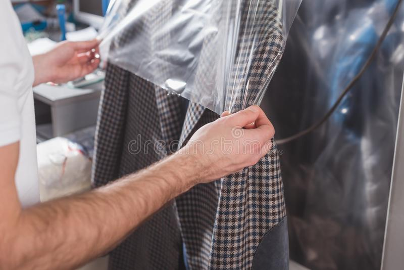 cropped shot of dry cleaning worker packing jacket royalty free stock photography