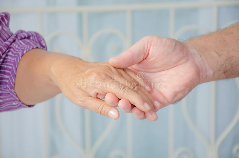 Cropped shot of elderly couple holding hands while sitting together at home, Concept of take care together, Focus on hands. A Cropped shot of elderly couple stock image
