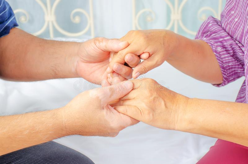 Cropped shot of elderly couple holding hands while sitting together at home, Concept of take care together, Focus on hands. A Cropped shot of elderly couple royalty free stock image