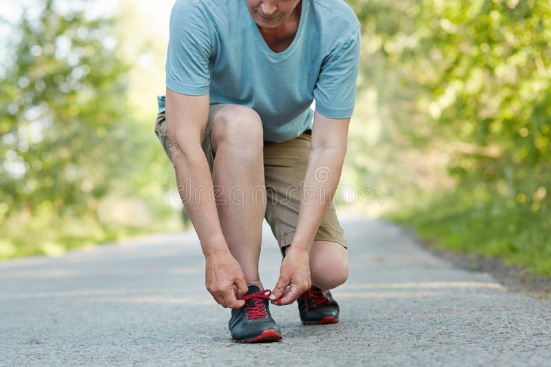 Cropped shot of elderly male athlete ties shoelaces, takes rest after jogging exercise, wears sportswear, poses outdoor. Man runne royalty free stock photography