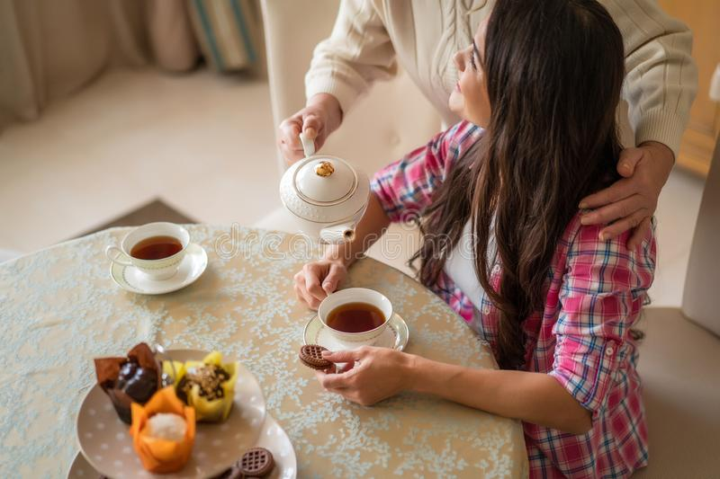 Senior woman pours tea from teapot into her daughter`s cup. Cropped Shot Of Elderly Woman Pouring Aromatic Tea From Wtire Ceramic Teapot Into Girl`s Cup. Family stock photo