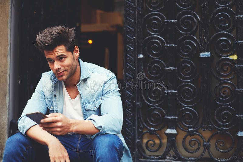 Cropped shot of a fashionable man using his mobile phone in urban setting royalty free stock photo