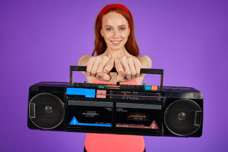 Cropped shot of female aerobics trainer holding portable retro cassette player. Cropped shot of female aerobics trainer stands with hands forward holding royalty free stock image