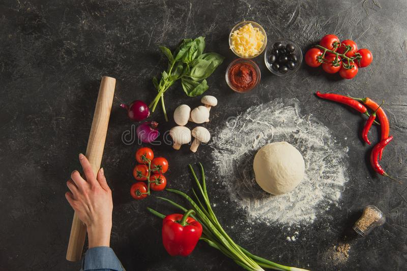 cropped shot of female hand, fresh ingredients and raw dough for italian pizza royalty free stock photography