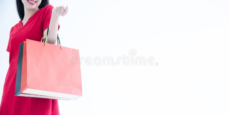 Cropped shot of female hand holding bunch of different colorful blank shopping bags over isolated white background. Many packets stock photo