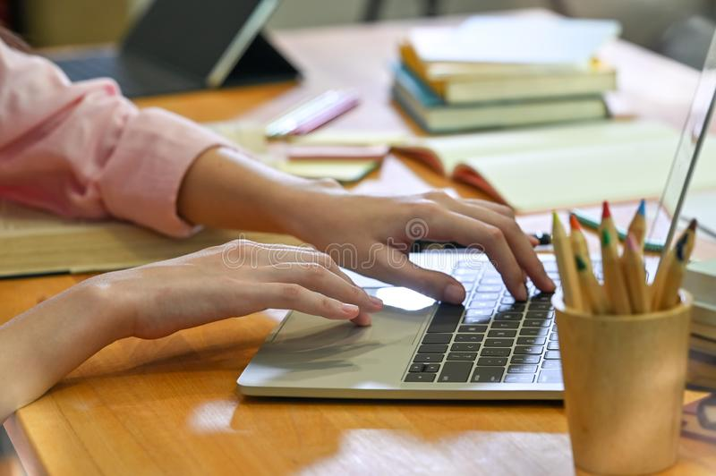 Cropped shot female hands using laptop computer on library table royalty free stock photos