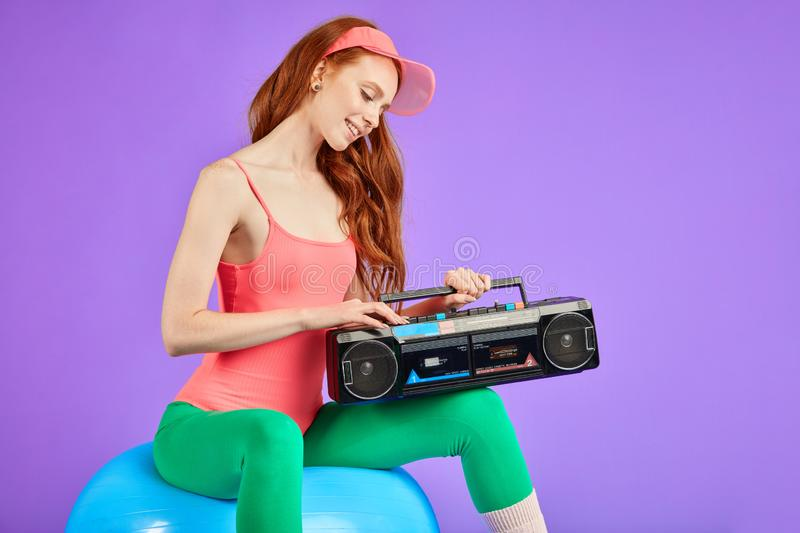 Cropped shot of fit and beautiful woman with portable cassette player. Cropped shot of fit and beautiful female singer with long red hair shooting her music royalty free stock image