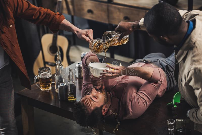 Cropped shot of friends pouring beer in funnel and man. Drinking while lying on table stock image