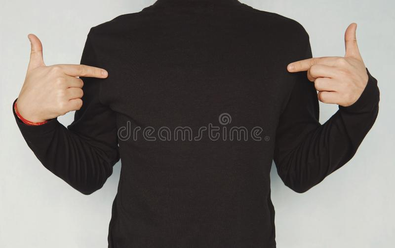 Cropped shot of good-looking young unshaven man wearing casual clothes, pointing fingers at copy space on his black blank t-shirt royalty free stock photo