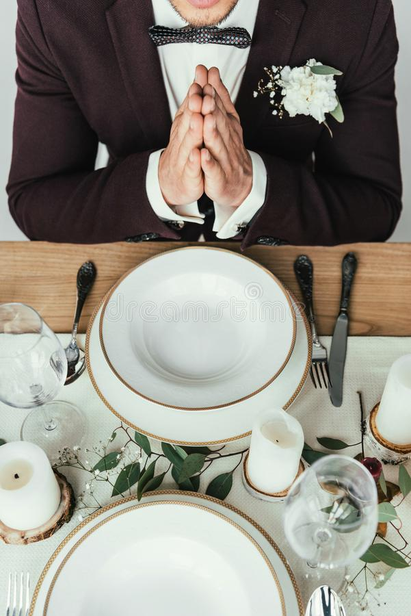 cropped shot of groom in suit praying while sitting at served table, rustic stock photos