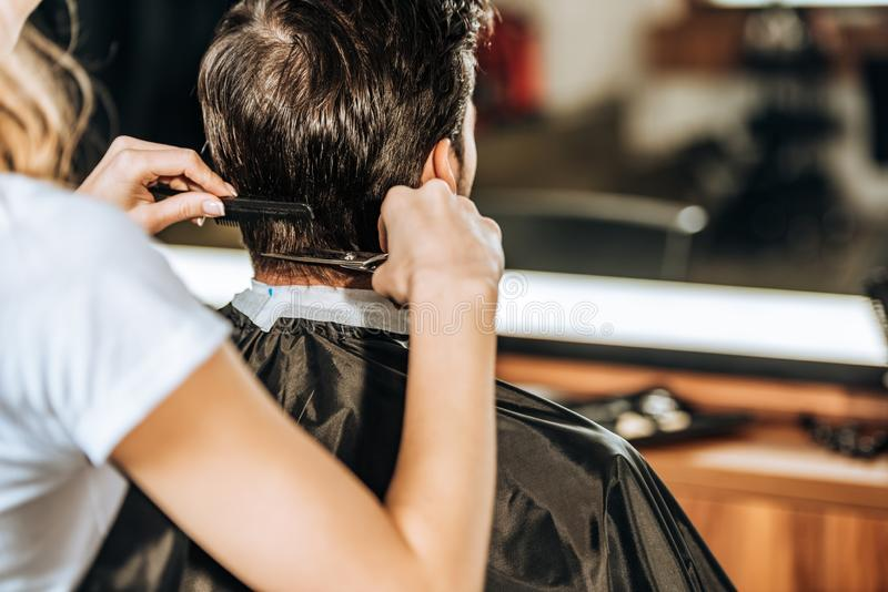 Cropped shot of hairdresser cutting hair to male client stock photography