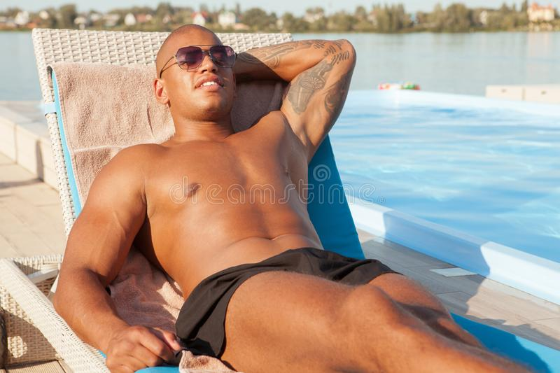 Handsome athletic African man sunbathing at the beach stock images