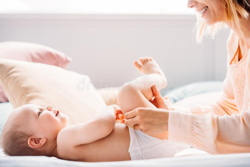 Cropped shot of happy mother putting diaper on little child. While he playing with toy stock photography