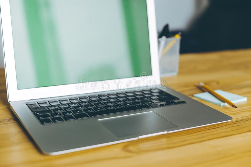 Cropped shot of laptop with blank screen on wooden table and sheet of paper with pen on it. royalty free stock images