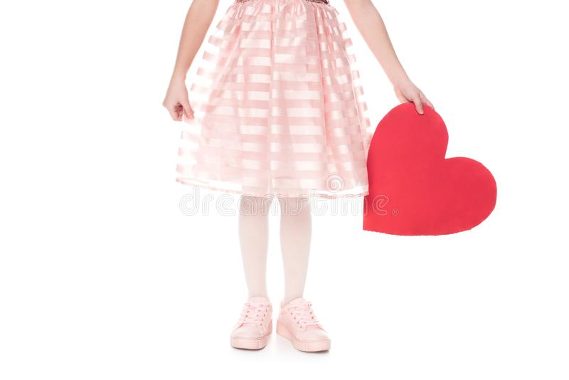 Cropped shot of little child in pink dress holding red heart symbol. Isolated on white stock illustration