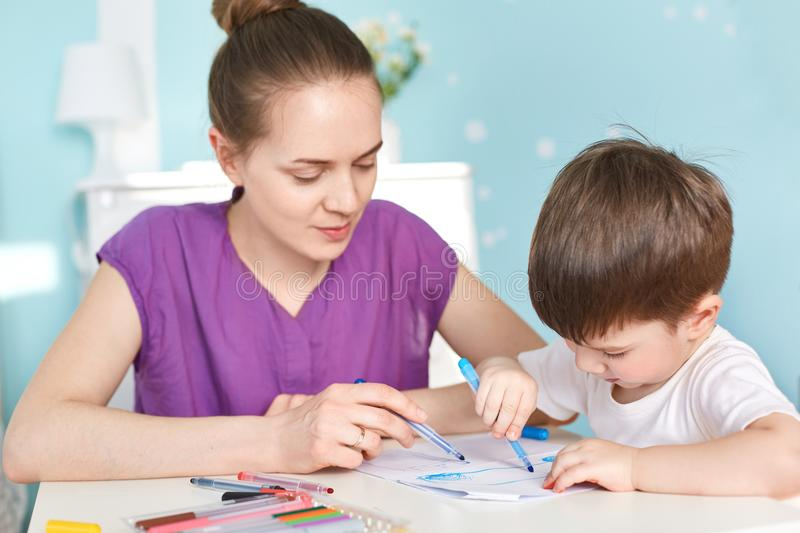Cropped shot of lovely young woman with attentive look sits next to her dark haired handsome son, prepares him to school and devel stock images
