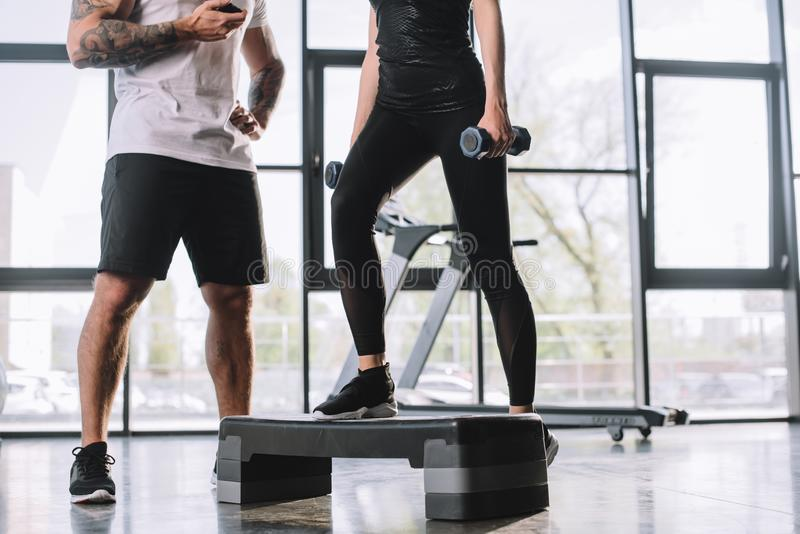 cropped shot of male personal trainer with timer and young sportswoman doing step aerobics exercise with dumbbells at gym royalty free stock photography