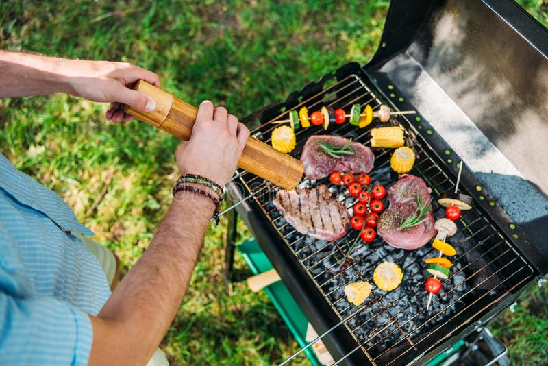 cropped shot of man with grinder cooking food on grill during barbecue stock photo