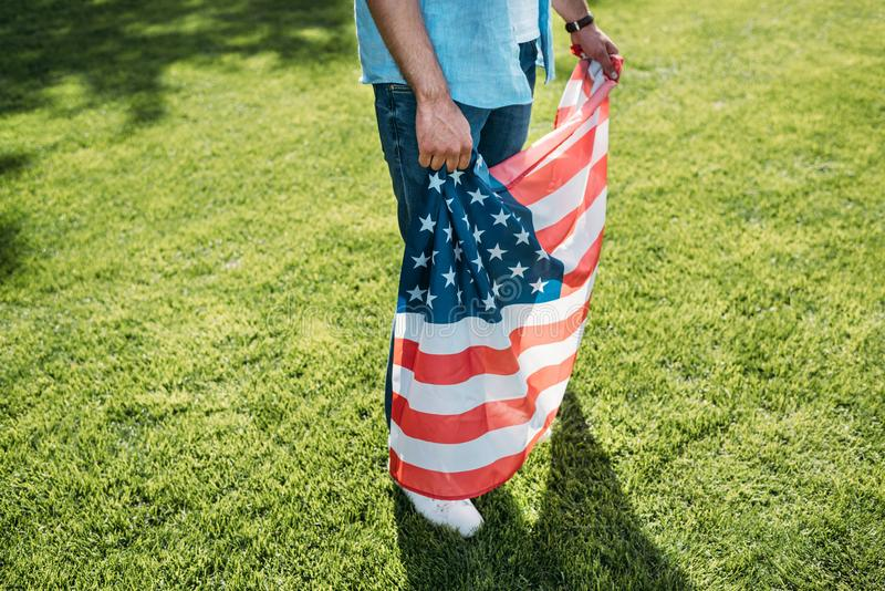 cropped shot of man holding american flag while standing on grass stock photo
