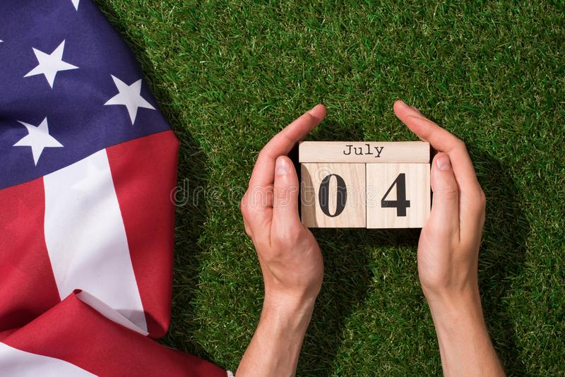 Cropped shot of man holding calendar with 4th july date with american flag on green grass, americas independence. Day concept royalty free stock image