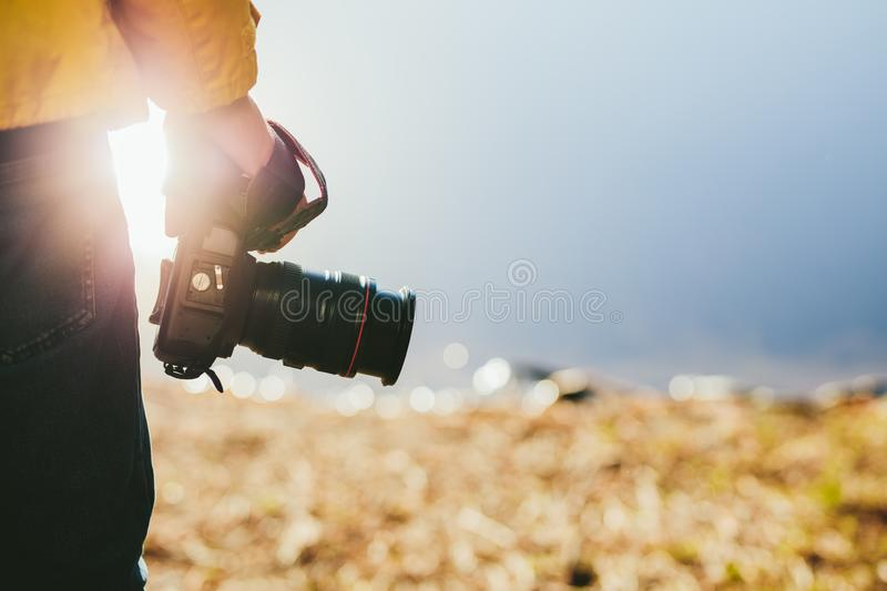 Cropped shot of a man holding a dslr camera. In his hand. Rear view close up of hand of a person holding a digital camera with sun flare in the background royalty free stock photos