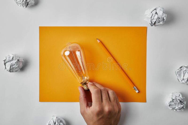 Cropped shot of man holding incandescent lamp on blank yellow paper with pencil surrounded with crumpled papers. On white surface royalty free stock photography
