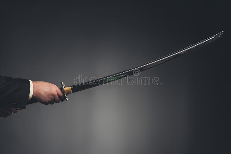 cropped shot of man holding katana sword stock image