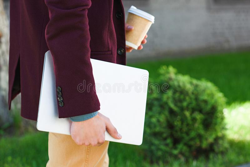 Cropped shot of man holding laptop and coffee to go. On street royalty free stock photo