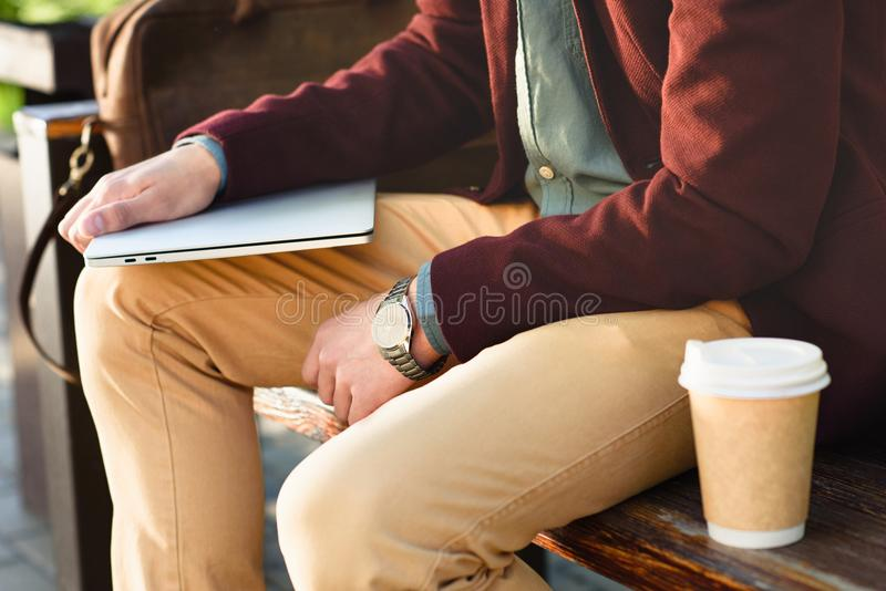 Cropped shot of man holding laptop and sitting. On bench stock photos