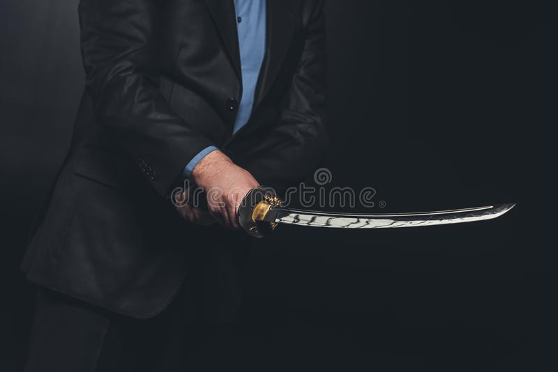 cropped shot of man in suit holding japanese katana sword stock photo