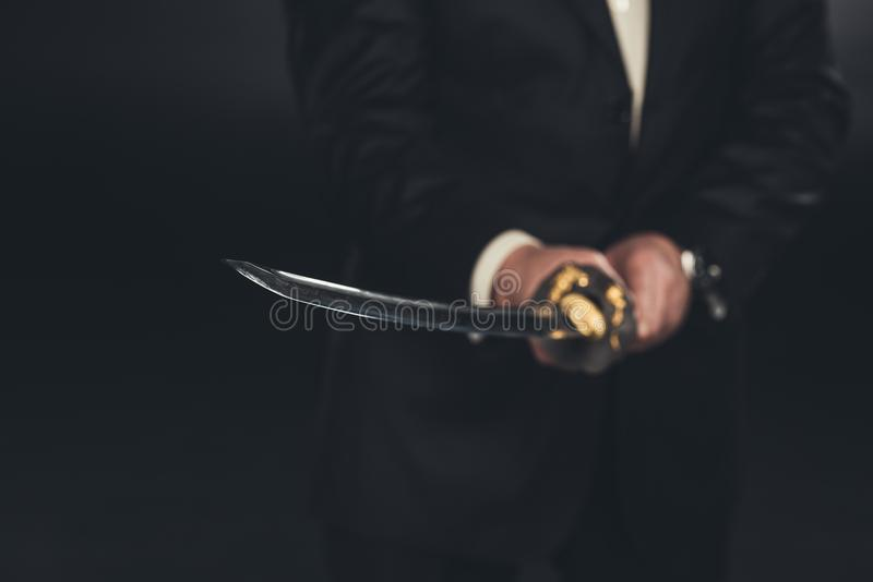 cropped shot of man in suit with katana sword royalty free stock images
