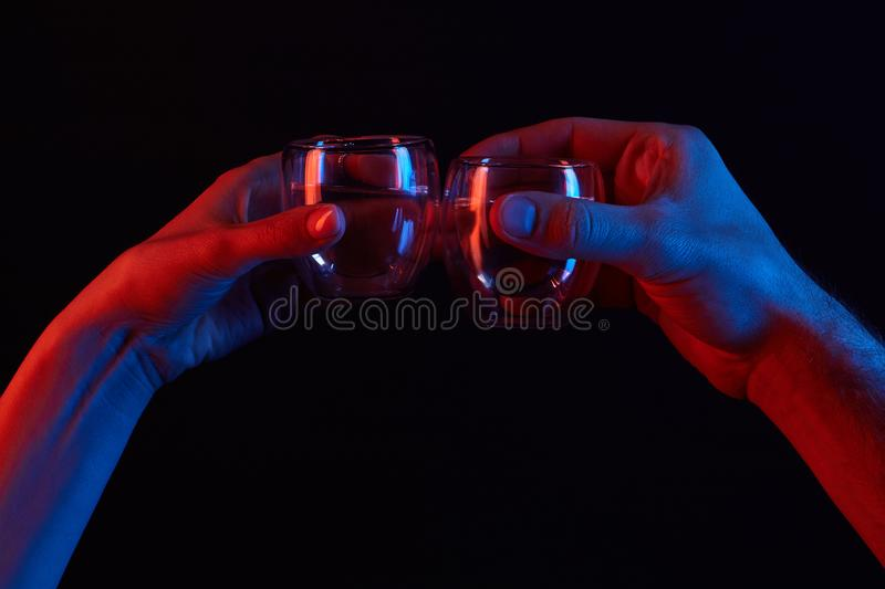 cropped shot of man and woman clinking glasses under toned light on black royalty free stock photos